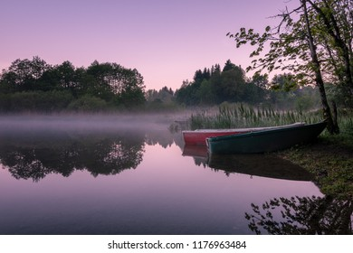 French landscape - Jura. View over the lake of Bonlieu in the Jura mountains (France) at sunset with two boats in the foreground.