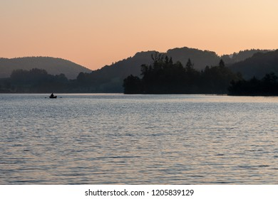 French landscape - Jura. View over the lake of Ilay in the Jura mountains (France) with fisherman in boat.