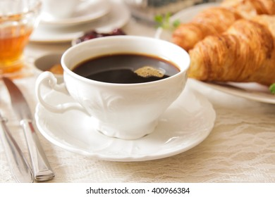 French light breakfast of coffee and croissants with jam honey on a light background