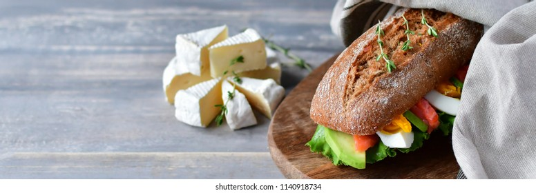 French lunch: sandwich from a cereal baguette with avocado, salmon, egg and lettuce leaves and Camembert cheese,  wooden table and dark background, selective focus