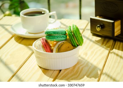french macaron and cup of coffee on wooden table.