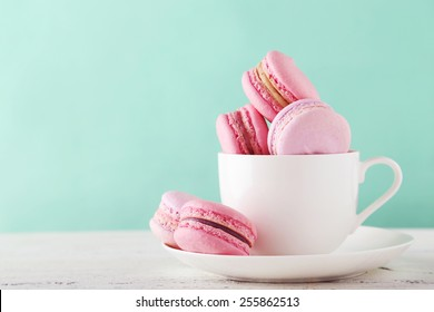 French macarons in cup on white wooden background.Toned image