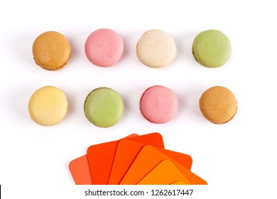 French macarons and red orange color swatches on white background