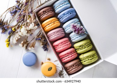 French macaroon cake. Macaroons in box with dried flowers on white background flat lay