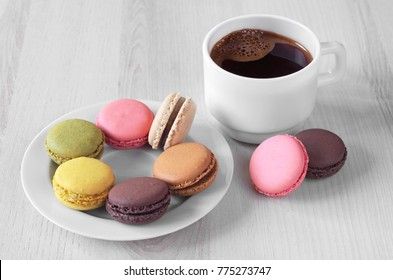 French macaroons in plate and cup of hot coffee on light wooden background