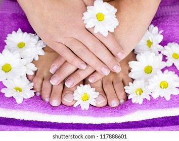 French manicure and flowers on a towel