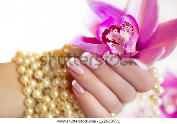 French manicure to a woman's hand with an Orchid and beads.