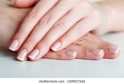 French manicured hand on white