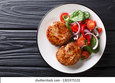 French meat balls crepinette served with fresh vegetable salad close-up on a plate. Horizontal top view from above