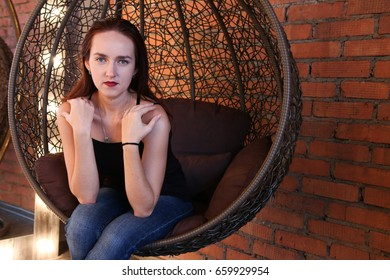 French model posing in a Chair and showing her shoulders.