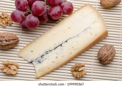 French Morbier cheese with grapes and walnuts on a straw placemat