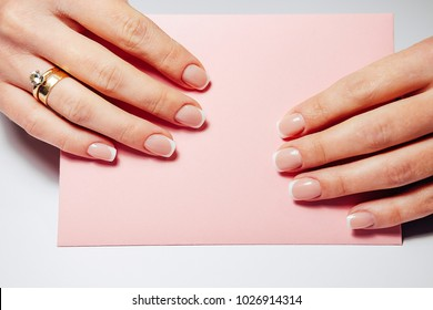 French nail extensions. Women with beautiful manicure and wedding ring holding a pink envelope with weding invitation.