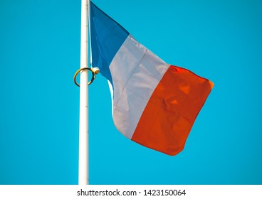 French national flag flying from a flagpole on a white flagpole in a close up view as it waves in the wind against a blue sky