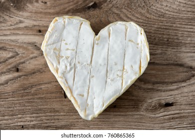 a French Neufchatel cheese shaped heart on a wooden table