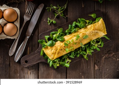 French omelet, fluffy, fresh eggs and herbs on wood board