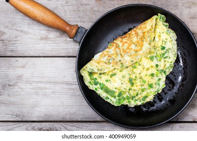 French omelet with herbs, cooked in a cast iron skillet. In a rustic style.  Top view, flat lay.
