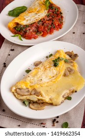 French omelet with mushrooms and cheese. Omelet with tomatoes. A large portion is served on a white plate. Close up and vertical orientation.