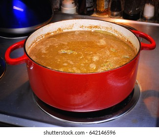 French onion soup simmering on a stove in a red enameled cast iron dutch oven