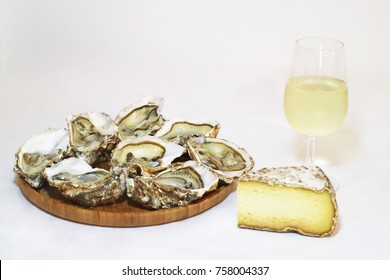 French oysters on a wooden plated with white wine and cheese on table
