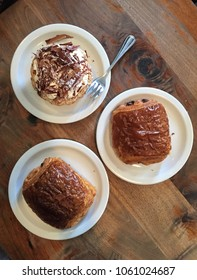 French pastry: Two pain au chocolat and one banana cream tarte on plates