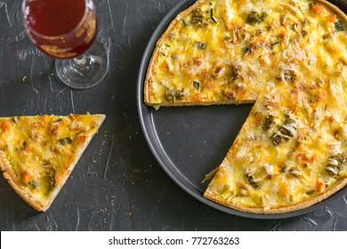French pie Quiche or Quiche lorraine - traditional open pie with salmon, cod, broccoli, egg, cheese, zucchini. Black table, top view