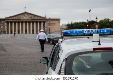 French police car and policeman walking in front of National Assembly in Paris.