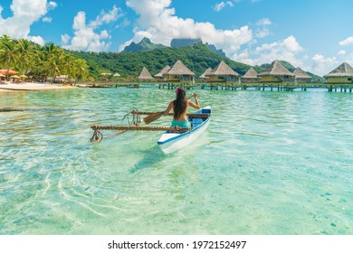 French Polynesia Tahiti travel vacation concept. Outrigger Canoe polynesian watersport sport woman paddling in traditional vaa boat. Water leisure activity, Bora Bora overwater bungalow resort hotel.