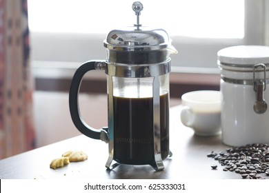 French press coffee maker on table top with white coffee cup and jar in warm morning light.