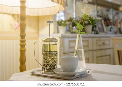 French press, a cup of tea and a white rose on the background of a cozy interior