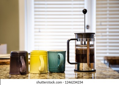 A french press on a kitchen counter top with coffee brewing and multi colored coffee mugs.