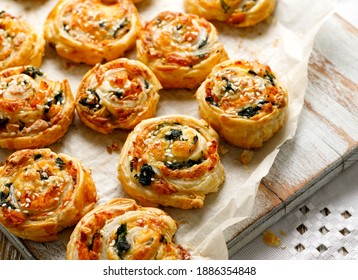 French Puff Pastry Pinwheels stuffed with salmon, cheese and spinach on on baking paper, close up view