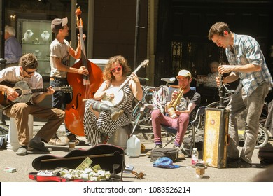 French Quarter, New Orleans, Louisiana, USA - March 31, 2018: Five-piece street band playing music in French Quarter, New Orleans. Instruments include banjo, bass, guitar, saxophone and trumpet.