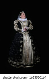French queen Marguerite of Navarre full height portrait on black background. Woman in reconstructed historical medieval royal costume of 16th century.
