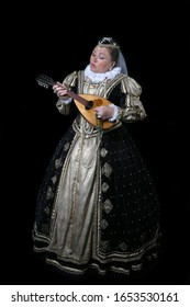 French queen Marguerite of Navarre plays mandolin on black background. Full height portrait of woman in reconstructed historical medieval royal costume of 16th century.