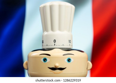 French restaurant symbol. Kitchen clock. French menu chef with mustache and toque on waving flag of France. Food delivery serving french specialties or baking. Traditional cooking and recipe - Image
