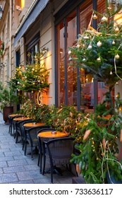 french restaurant - tables and chairs on the street of Paris, France, decorated with christmas trees and baubles