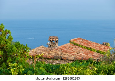 French Riviera: Scenic view of mediterranean coastline with medieval rooftop in foreground and space for text