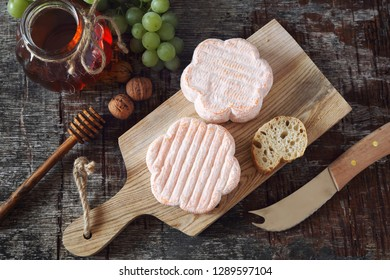French Saint Albray cheese, honey and slices of baduette on wooden cutting board, rustic style, top view