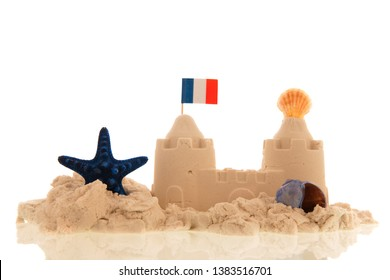 French sandcastle with red toys and flags isolated over white background