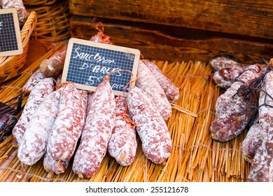 French saucissons and ham display in market in south of France, Arles, Provence. Local organic food.