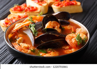 French seafood bouillabaisse soup closeup in a bowl served with toast on the table. horizontal