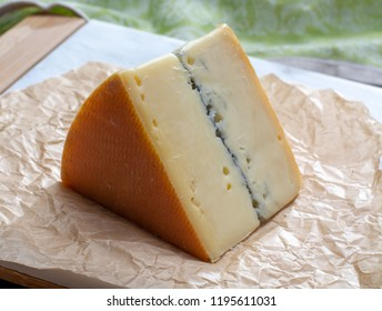 French semi-soft cow milk cheese morbier from Franche-Comte region with thin black layer and strong aroma  close up