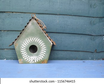 A French shabby chic style decorative green metal birdhouse on a blue wooden bench with wood panel background , a colourful garden decoration