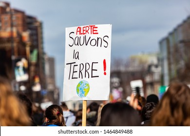 French sign held at ecological protest. A French sign is viewed close-up above the heads of environmental demonstrators, saying Alert, save the earth during a gathering in a city center.