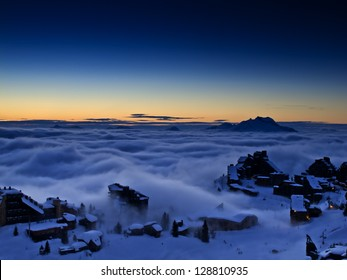 French ski resort Avoriaz in the area of Haute Savoie embedded in clouds by the sunset