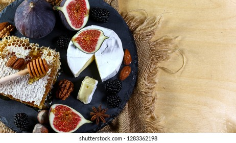 French soft Camembert cheese, original Camembert de Normandie served with fresh ripe figs, close up. Top view. Copy space.
