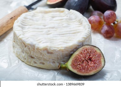 French soft Camembert cheese, original Camembert de Normandie served with fresh ripe figs and grapes, close up