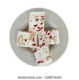French soft nougat with strawberry flawour and almonds isolated on white background. Greek manolato.