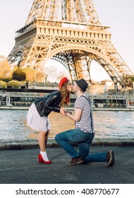 French stereotypical couple happy proposal under the Eiffel Tower in Paris, France