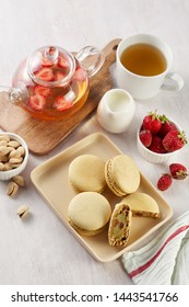 French strawberry pistachio macaron with berries tea. Afternoon tea still life. Close Up top view